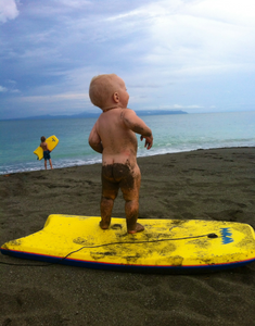Blonde baby with a sandy bottom standing on a yellow boogie board on a beach in Costa Rica's Osa Peninsula