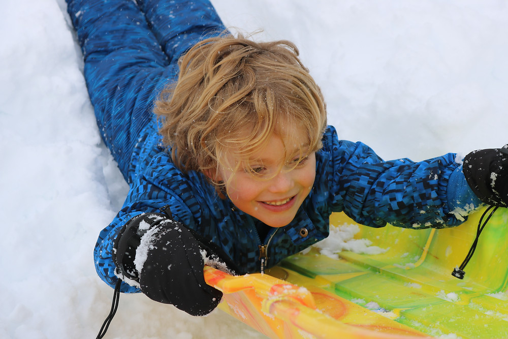 A smiling blonde boy in a blue snow suit being pulled through the snow on a yellow and green sled.
