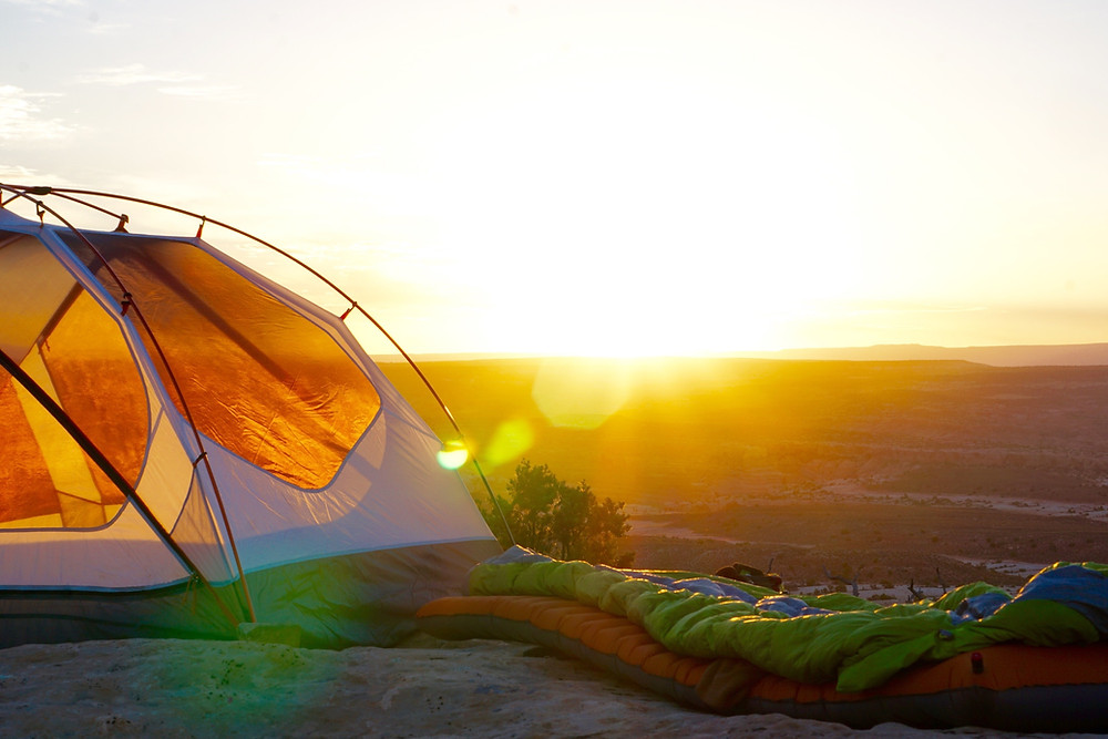 An orange and white tent next to green and orange sleeping bags on top of a bluff at sunrise.