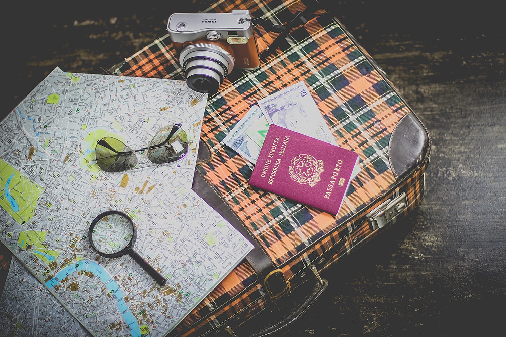 Suitcase, maps, camera, passport and money for organized travel