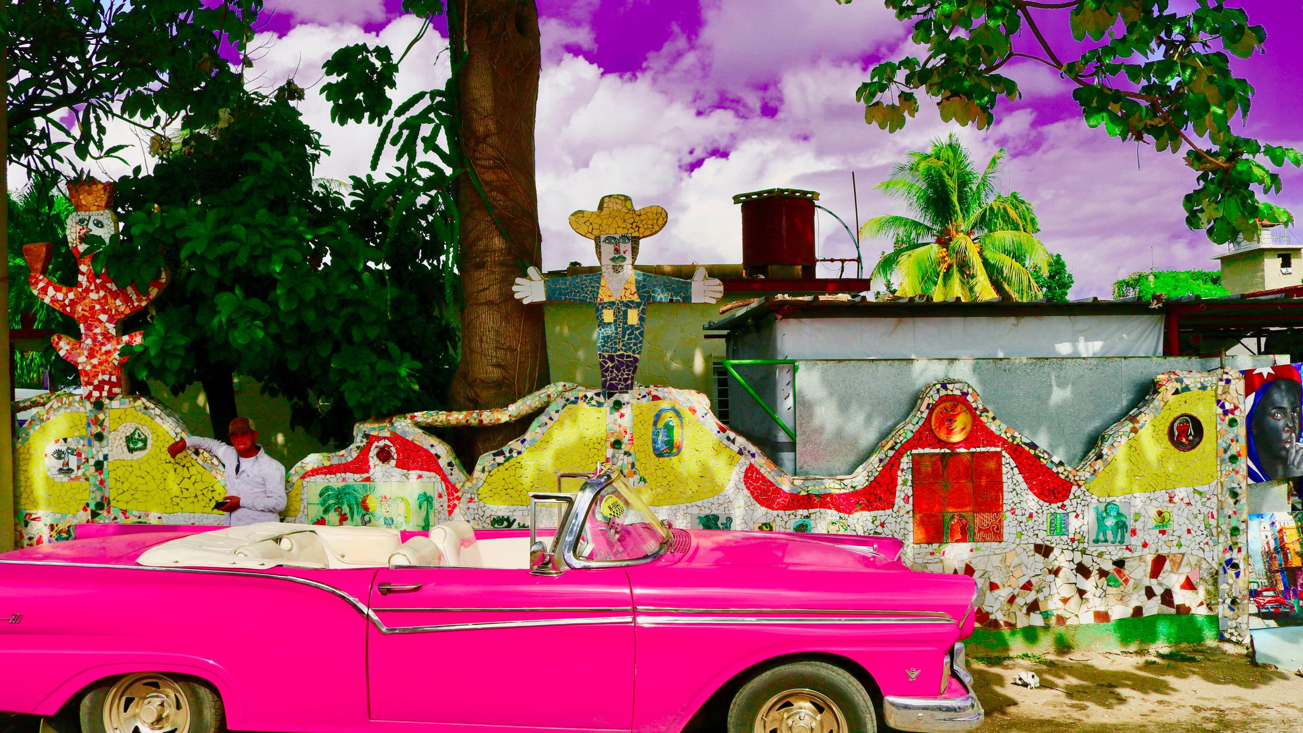 Hot pink Cadillac in front of Fusterlandia in Havana.