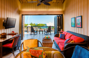A colorful living room at Barefoot Divers in Roatan that opens up to a porch with rocking chairs and a view of the Caribbean and a sailboat.