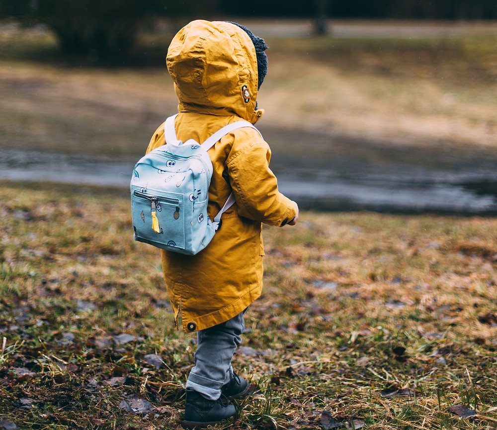 Toddler in yellow jacket and small blue backpack during a hike.