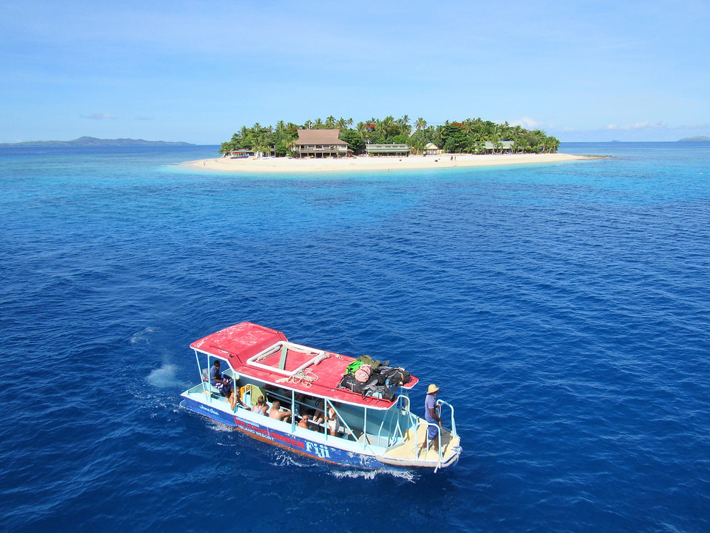 Scuba diving boat with red roof floating in front of a small atoll in Yasawa Islands, Fiji.