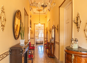 The elegant yellow, gold and wooden hallway of the La Villa Teresa casa particular in Havana. This is best budget accommodations in the city.