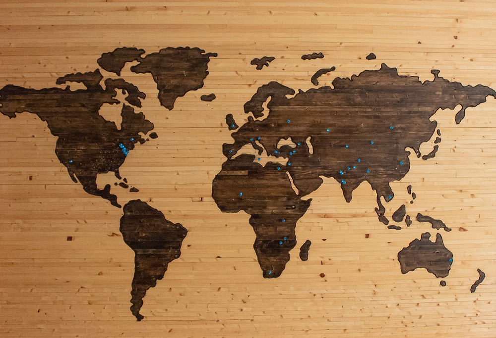 Wooden map of the world with blue pins in indicating areas that have been explored.