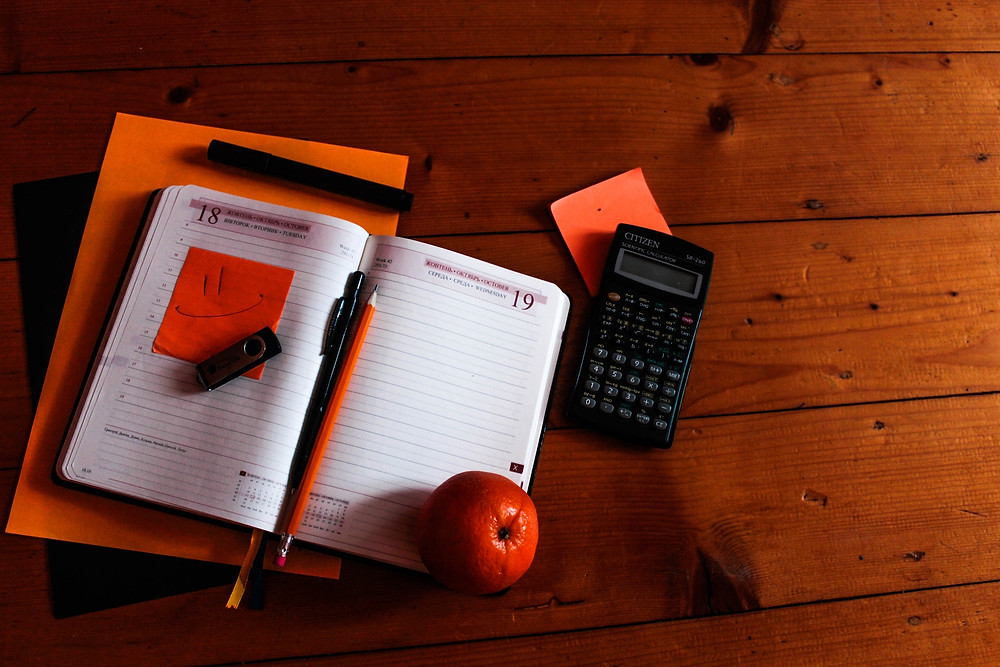 Day planner with a memory stick and orange sticky note on it, beside a calculator and an orange on a wooden table.