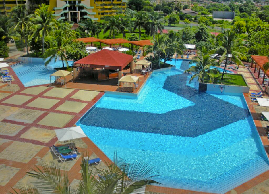 Large blue-tiled pools beside the red and beige patio at Memories Miramar Habana in Cuba.