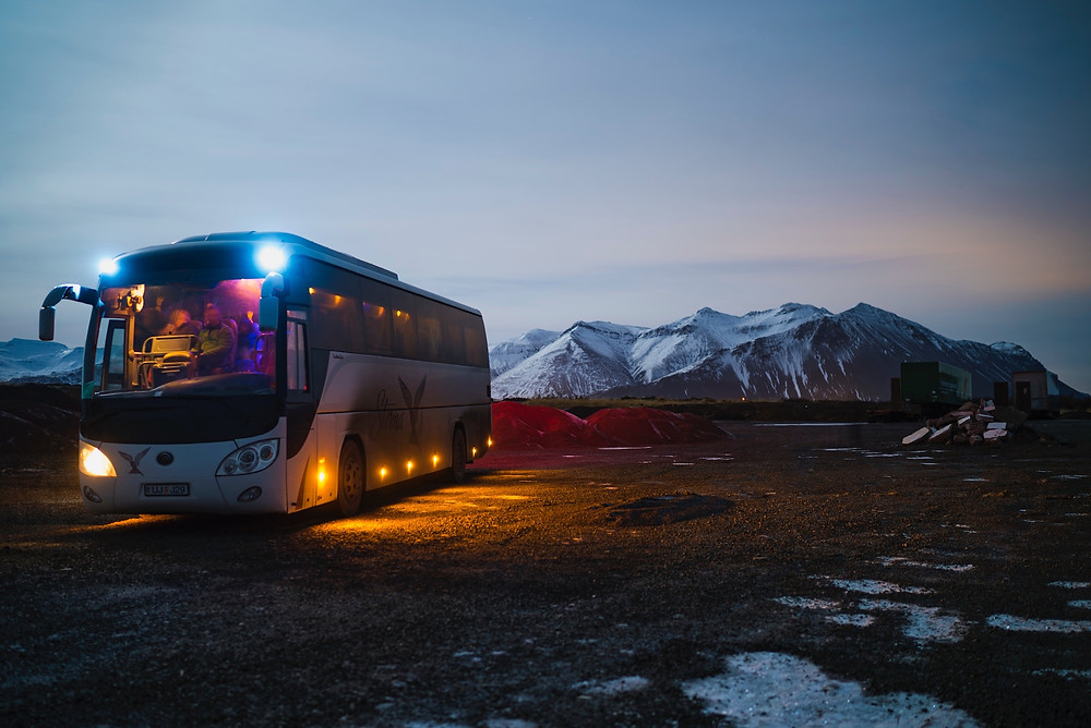 Bus in front of snowy mountains being used for long distance commutes for a family vacation