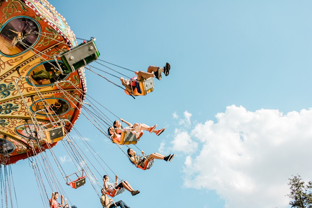 People on an amusement park swing ride that used sunscreen from their packing list