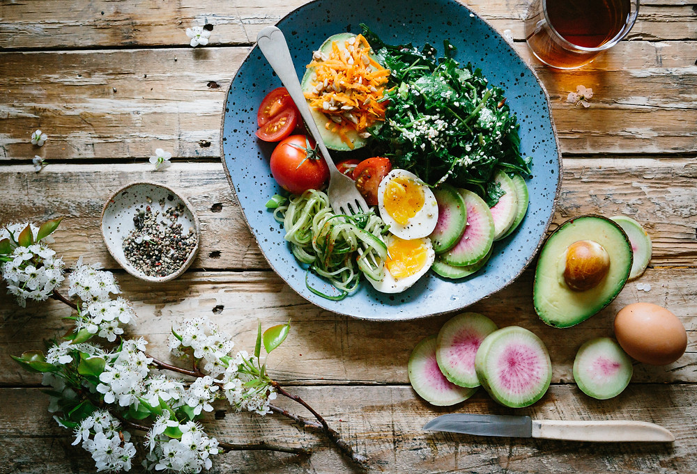 Eggs, avocado, tomatoes and other healthy vegetables in a blue bowl on a wooden table