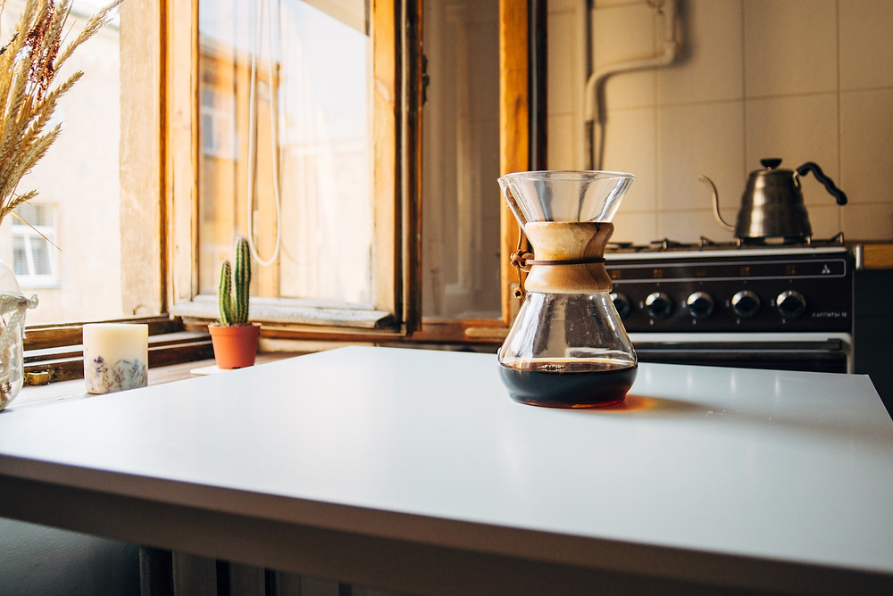 Coffee on a kitchen counter and a kettle on a stove that has been turned off in preparation for travel