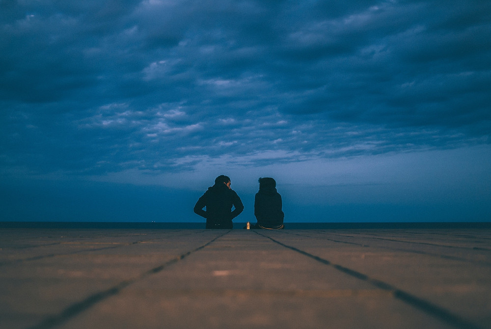 Two people in black sweaters sitting on a sea wall in Nicaragua and talking under a cloudy sky in the evening