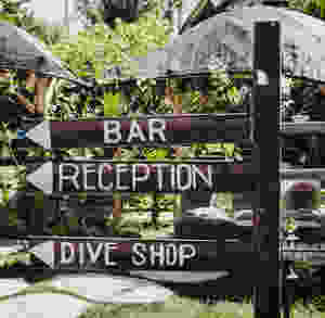 Wooden post sign on Roatan that says bar, reception and dive shop.