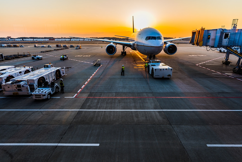 Airplane on a tarmac at sunset.