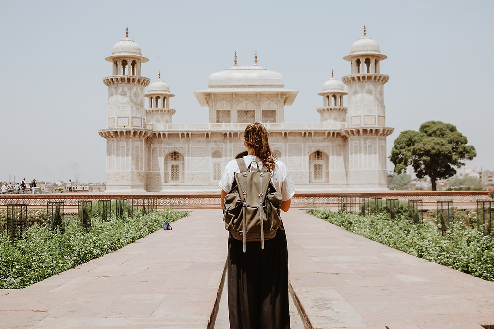 Brunette woman in black skirt and a white shirt, wearing a backpack, and standing in front of a temple while traveling.