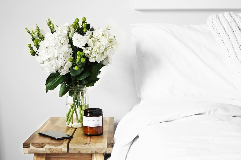 Bedside table with flowers and white bed used to adjust your sleep schedule before a trip