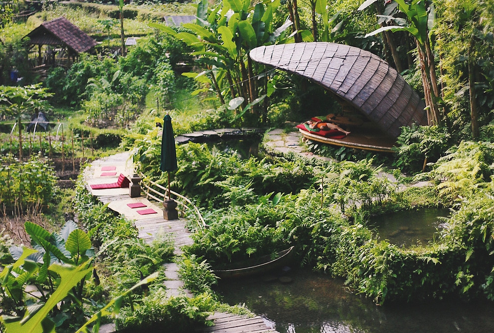 Woman lying in a shaded enclosure at a lush eco-friendly hotel in Bali