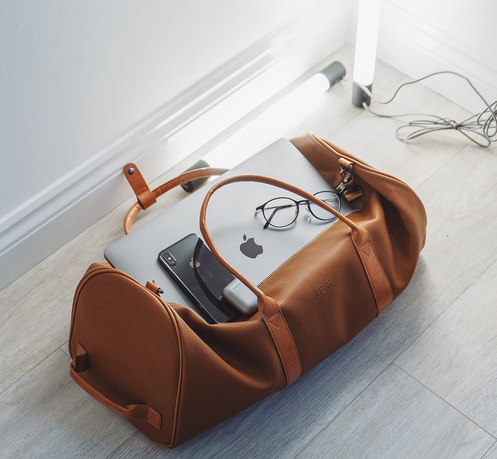 Travel leather duffel bag with a silver MacBook Pro, black iPhone and glasses in it.