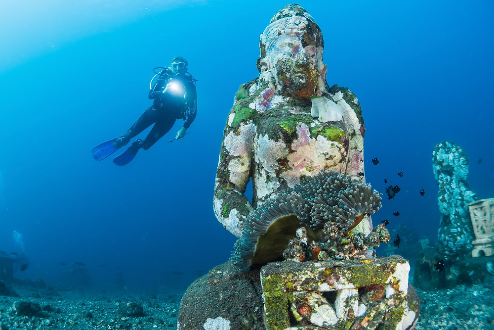 Person scuba diving near a sculpture during a vacation