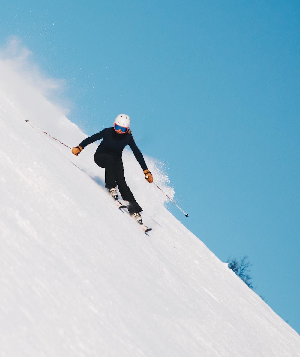 Woman skiing black diamond ski run during all mountain ski clinic at Mammoth Mountain