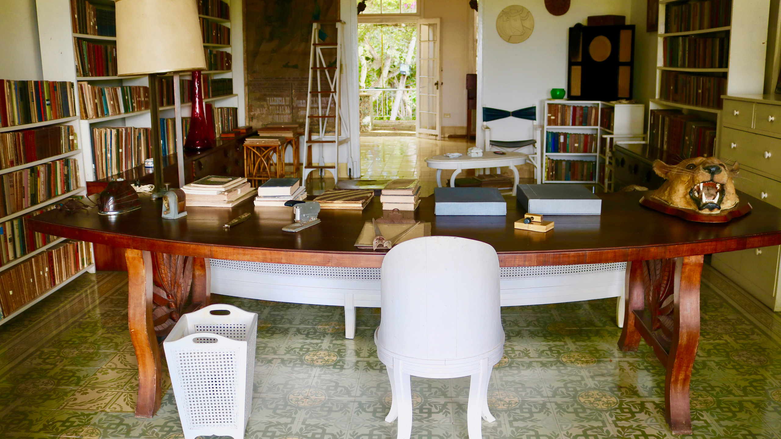 Large desk with white chair surrounded by bookshelves in Ernest Hemingway's Finca Vigia home in Cuba.