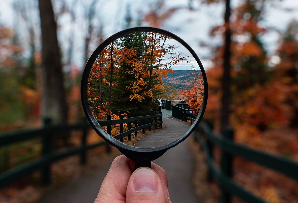 A man holding a magnifying glass up to a hiking trail with trees with red and orange leaves in the Fall.