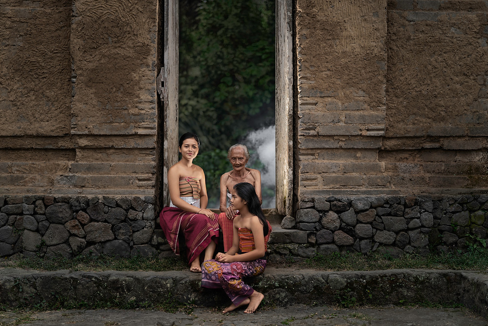 Three native women sitting in a doorway of a wooden structure in Tenganan, Bali.