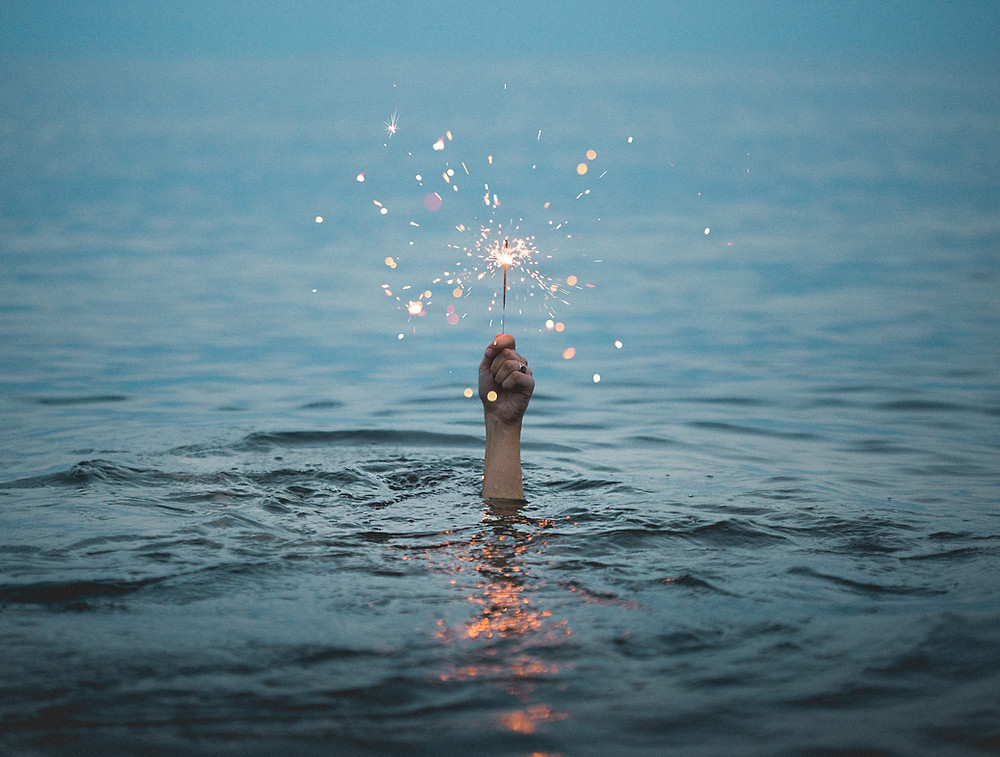A woman's hand sticking out of dark blue water in Nicaragua and holding a lit sparkler
