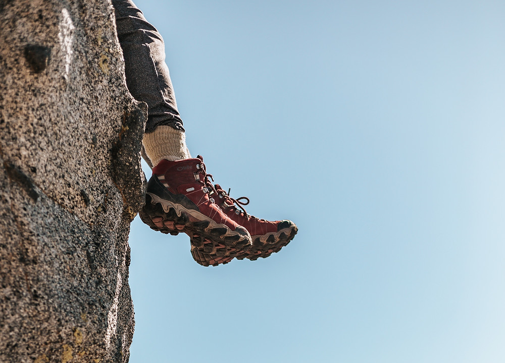 Person with red and black hiking boots dangling their legs off a rock boulder.