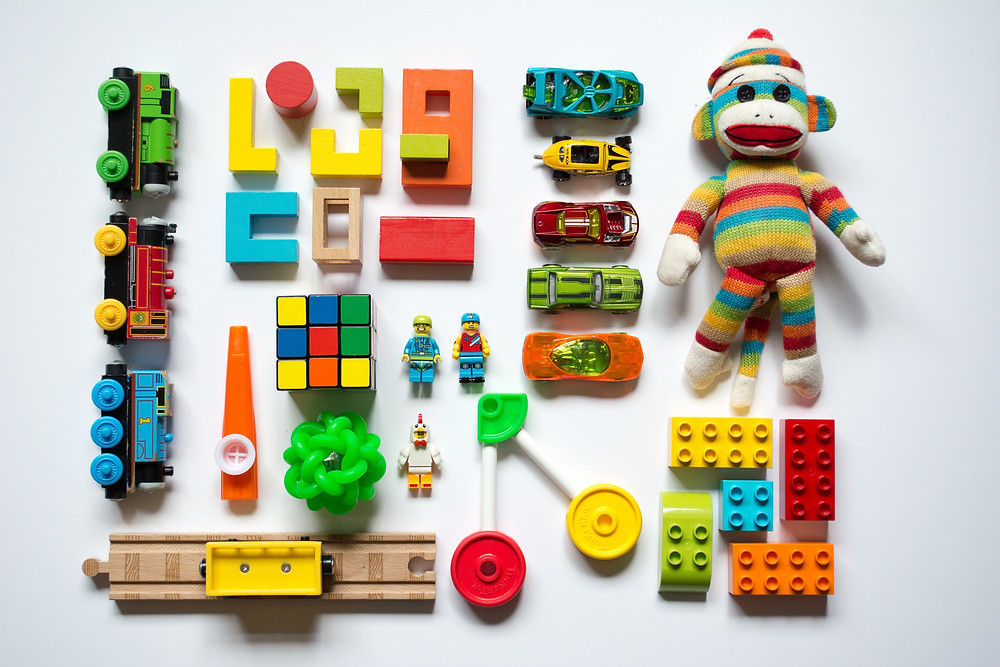 Flat lay with brightly colored toy cars, blocks, trains, Legos, and a monkey stuffed animal for airplane travel with kids.