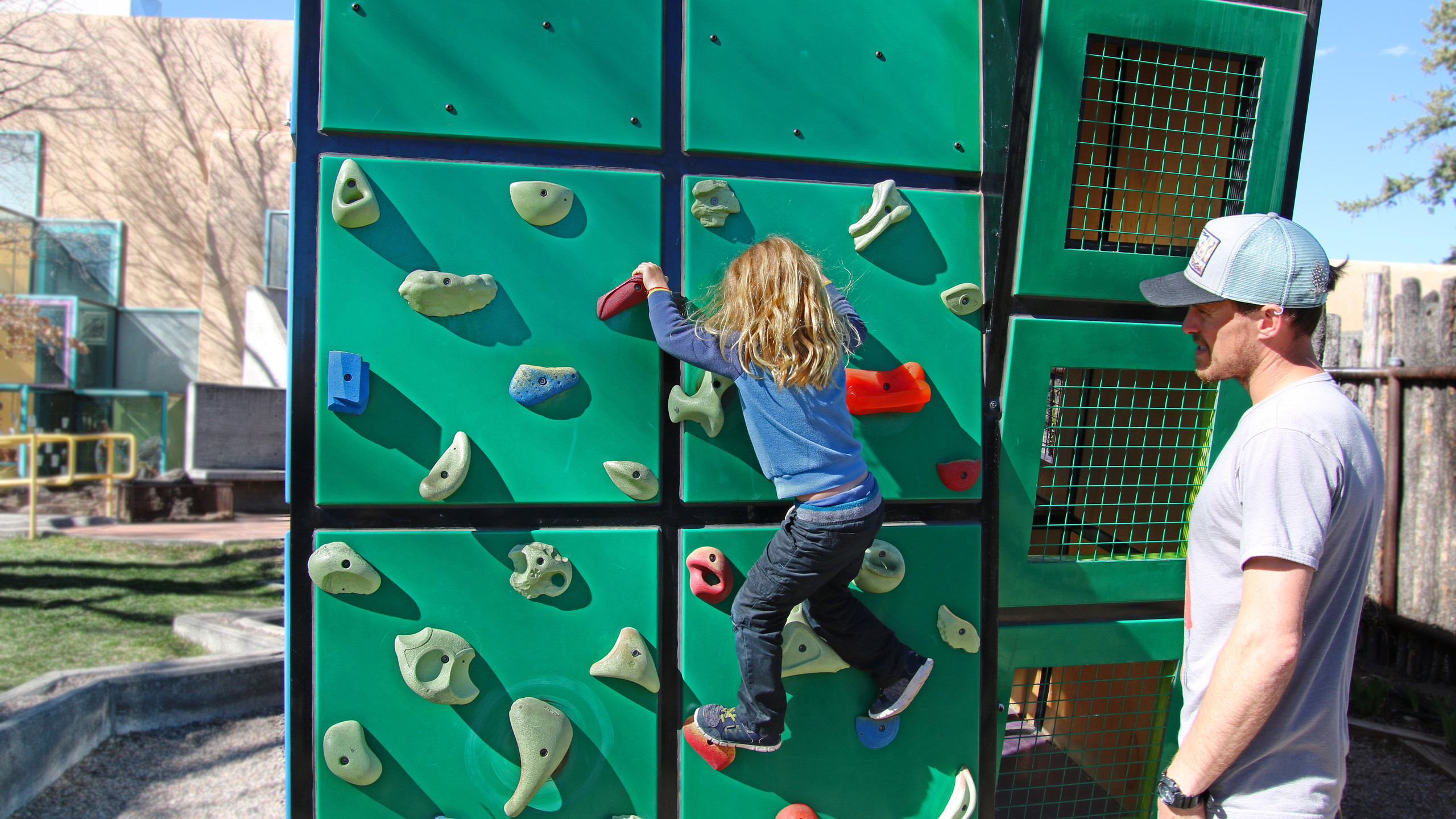Blonde boy in blue shirt and black pants climbing the green climbing wall at the Santa Fe Children's Museum while his dad spots him