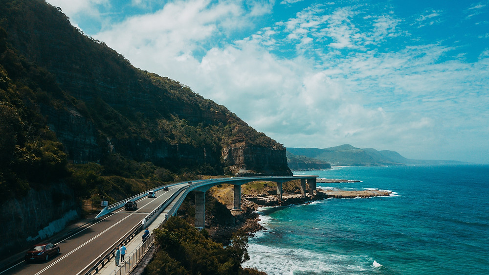 Cars driving on a highway by the ocean and mountains under a blue sky with white clouds