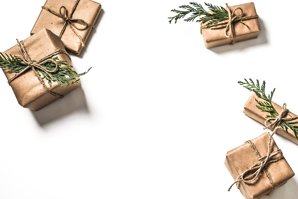 Small gifts wrapped in gold paper and topped with evergreen sprigs.