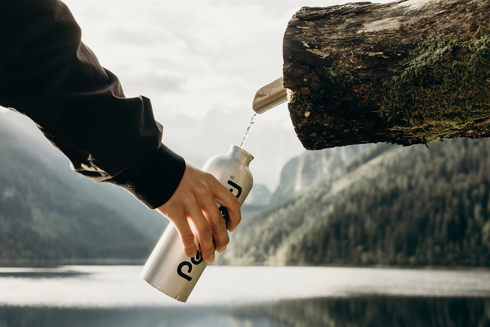 Man filling a silver, metal water bottle from a spout coming out of a log beside a lake during a hike.