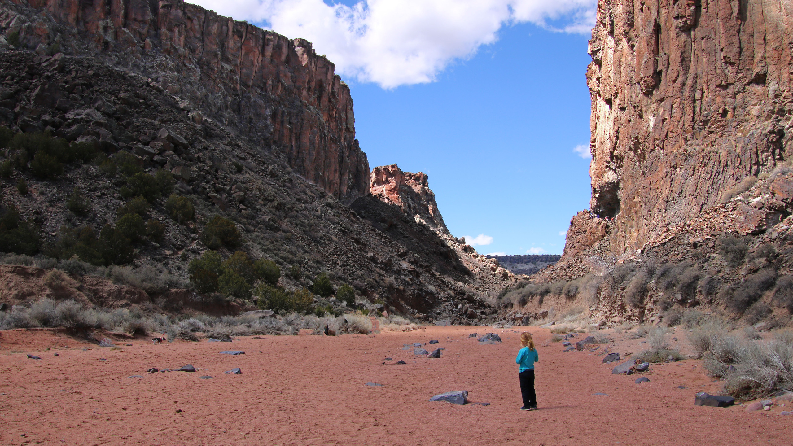 Little boy in blue shirt at the red base of Diablo Canyon in Santa Fe, New