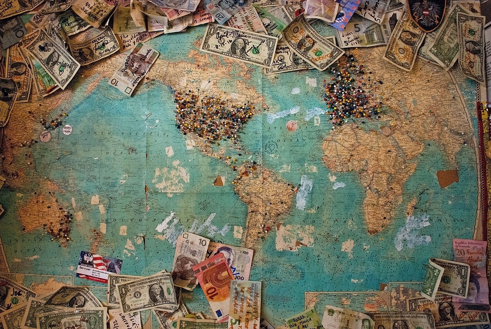 Map of the world with money for a travel budget pinned to it