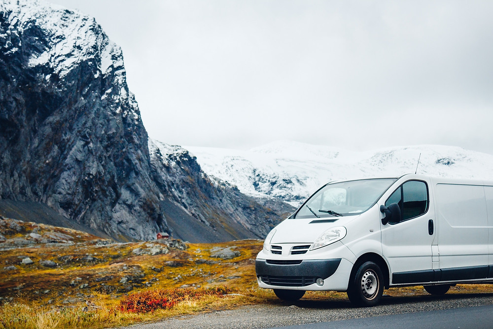 White van in front of snowy mountain reminding people to book transportation before a trip