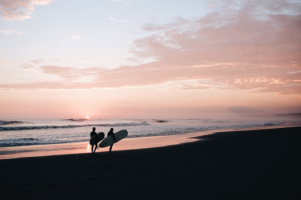 Two people holding surfboards and walking down a beach in Mancora, Peru at sunset.