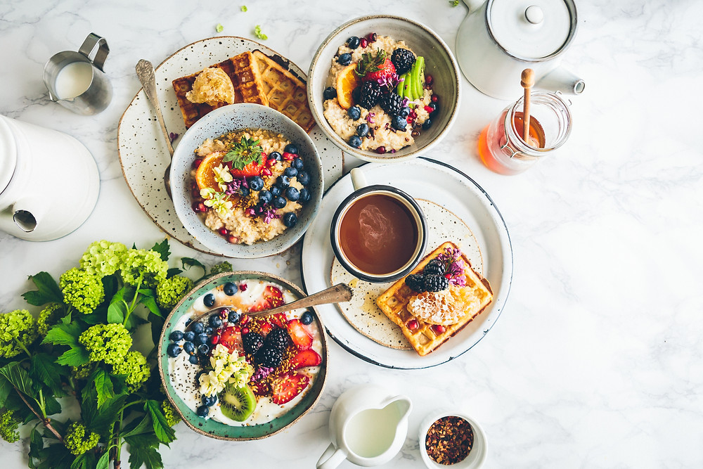 A marble table covered in breakfast food like waffles and oatmeal covered in fresh fruit.