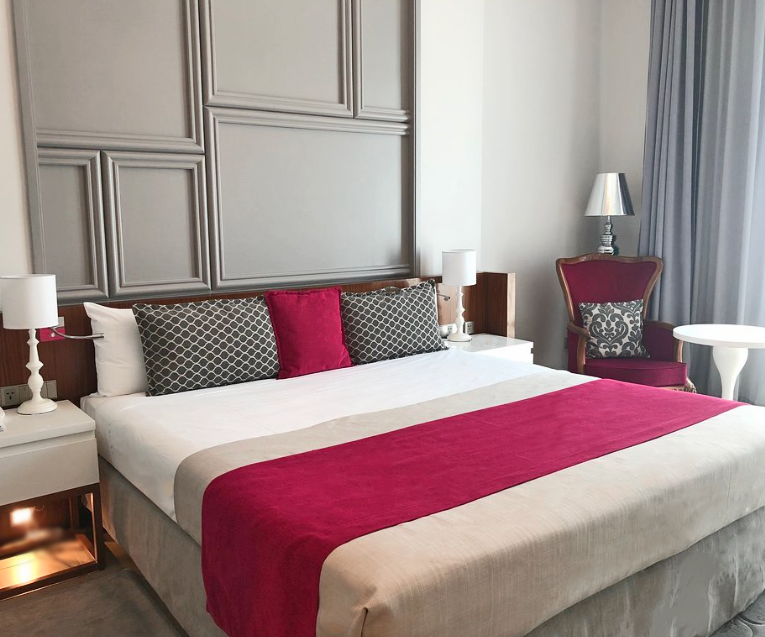 Luxurious room in the Gran Hotel Manzana Kempinski La Habana with a red and white comforter on the bed.