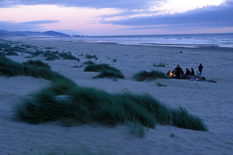A family having a sunset bonfire at Nehalem Bay State Park beach.