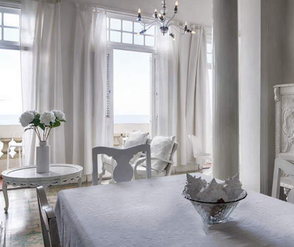 The all white interior of a room in Magical B & B by the Sea Havana that looks out to the sea.