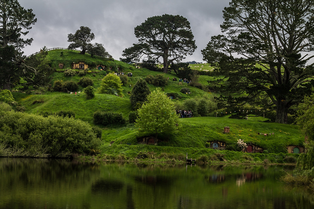 Wooden hobbit doorways on the lush hillside at Hobbiton in New Zealand. It's also known as The Shire from Lord of the RIngs.