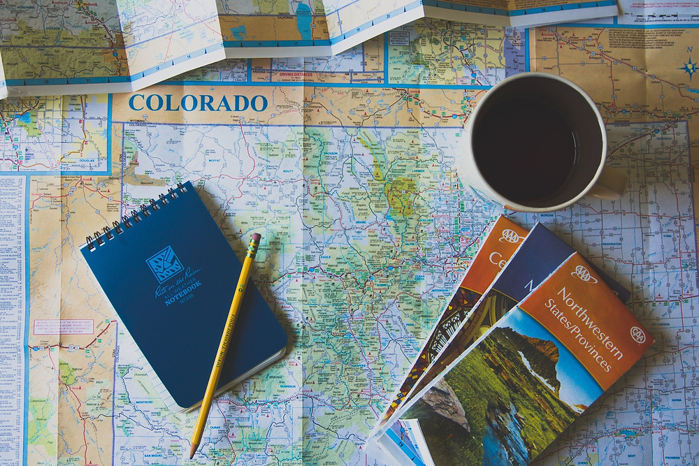 Maps and notebook being used to plan a family trip itinerary
