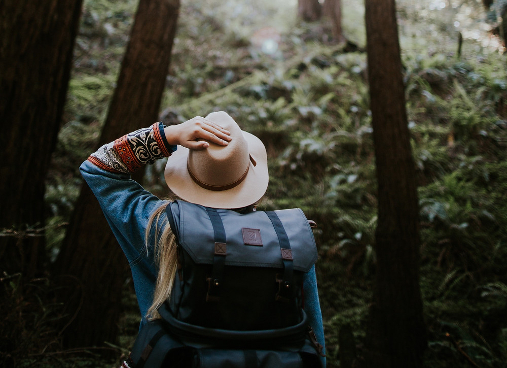 Woman with a wide-brimmed hat, jacket and blue packing hiking in the Pacific Northwest.