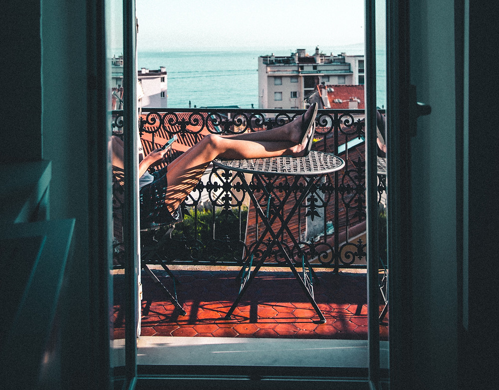 Woman sitting on a balcony with her legs resting on a table as she scrolls through her phone.
