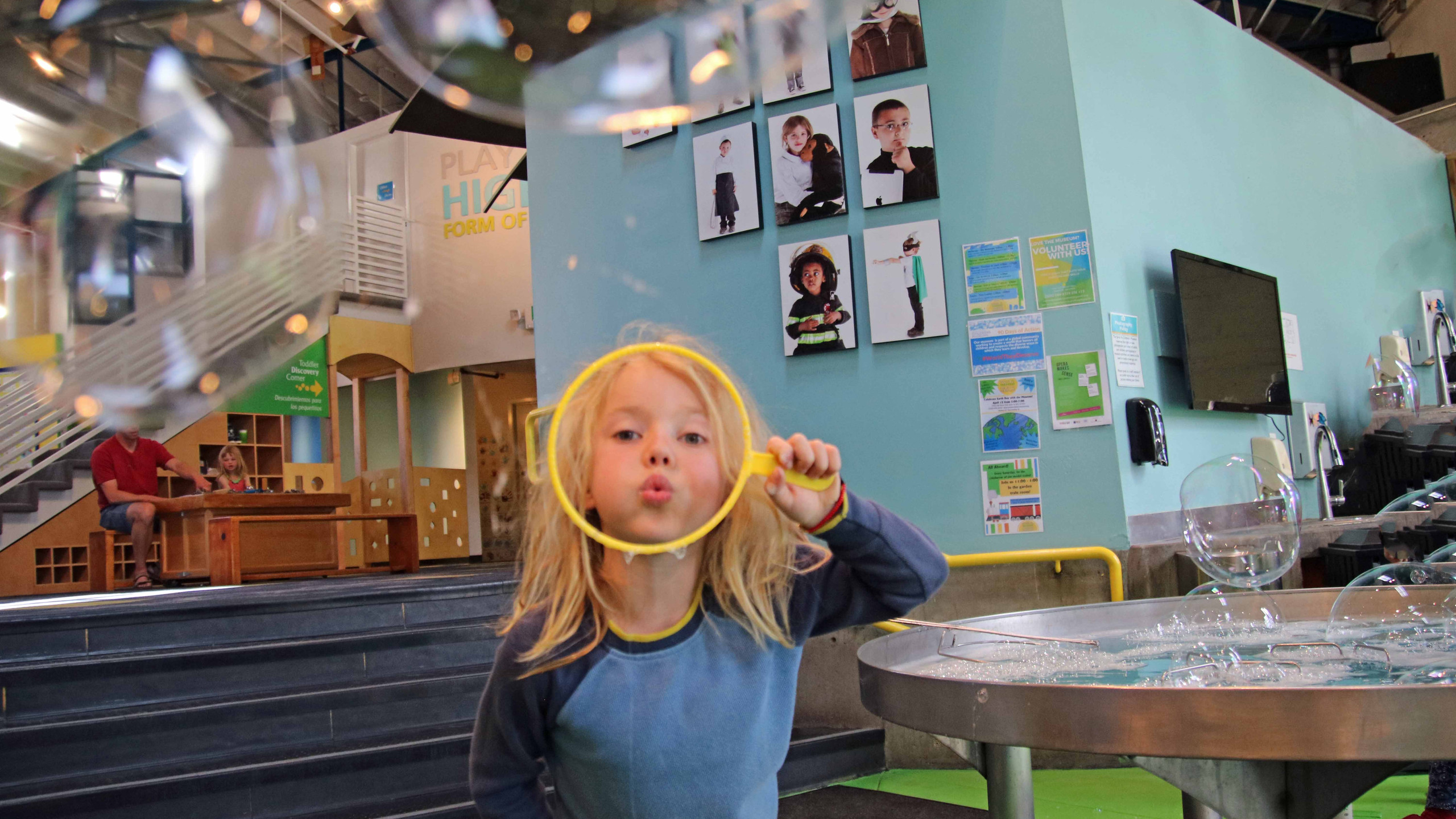 Blonde boy in blue shirt blowing a bubble at the bubble area at the Santa Fe Children's Museum