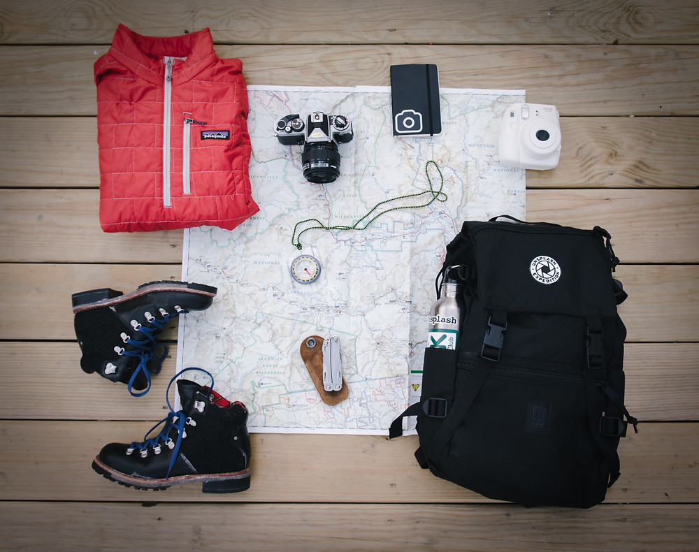 A red jacket, hiking boots, a black backpack, compass, and camera on a map beng packed for a camping trip.
