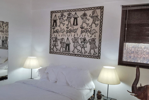 White bed in Havana's Cristo 34 casa particular, with tribal art above the bed.